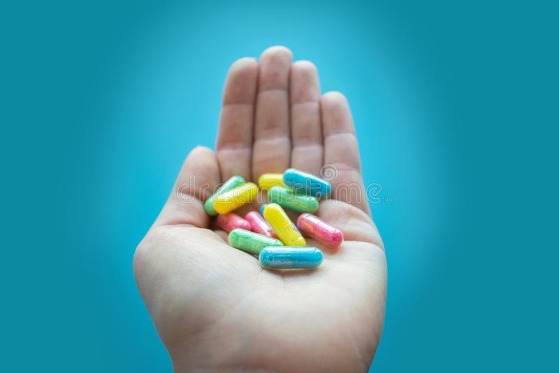 Colorful pills and medicines in the female hand on a blue background. Different pills and another drugs capsules for illegal stock image