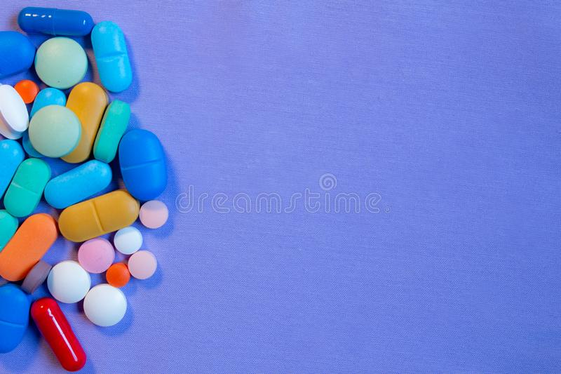 Colorful pills on neutral blue background. Some Colorful pills on neutral blue background royalty free stock images