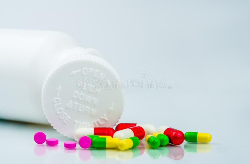 Colorful pills on white background and plastic bottle with blank label and copy space. Childproof packaging. Child resistant pill royalty free stock image