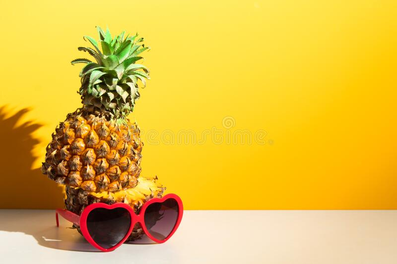 Colorful pineapple tropical fruit nature with fashion red heart love sunglasses, hot summer season vacation holiday. Yellow background wallpaper stock image