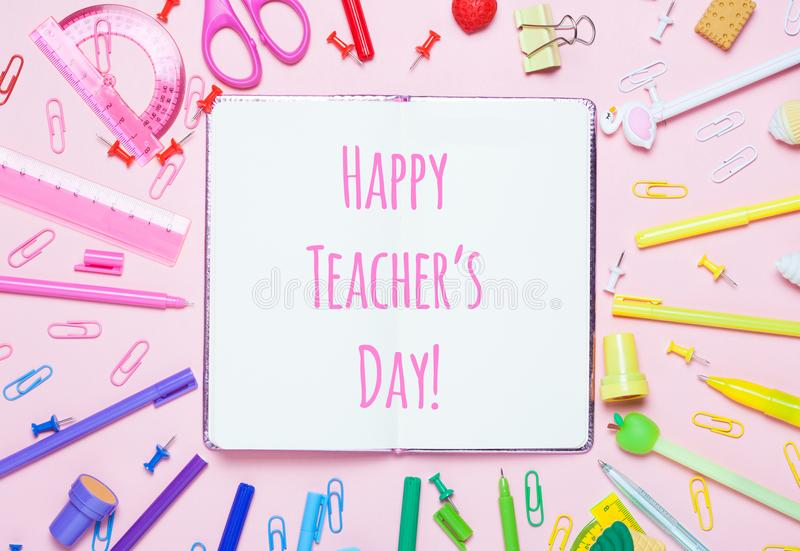 Various School accessories are laid out in the form of a rainbow, Happy Teacher`s day text. royalty free stock photos