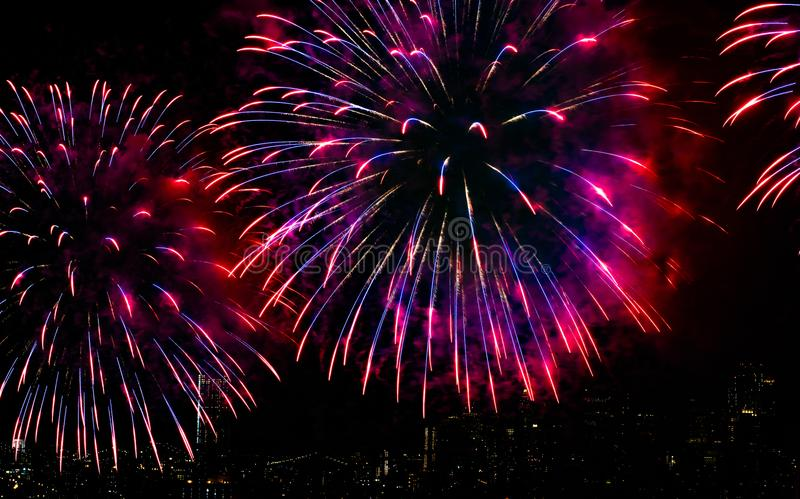 Colorful Fireworks Over City Skyline and River with Black Sky Background stock images