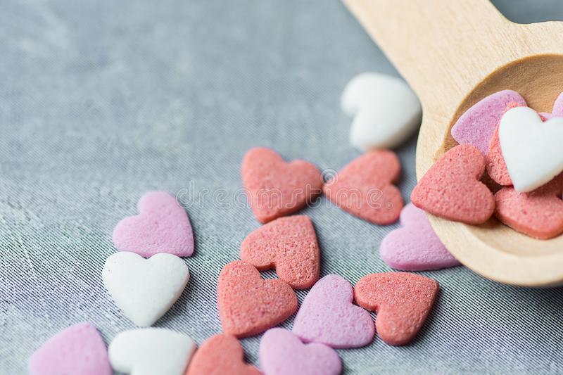 Colorful Pink Red White Sugar Sprinkles Candies Spilled from Small Wood Spoon on Grey Background. Valentines stock photography