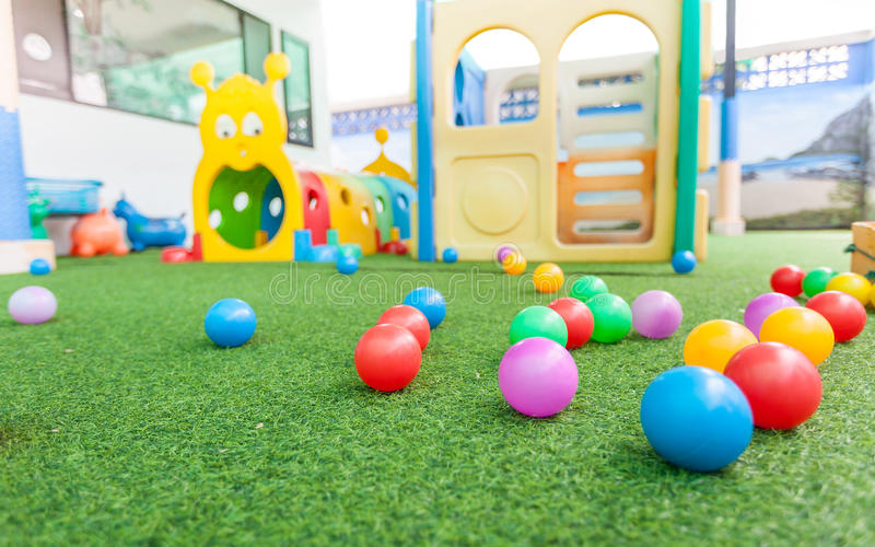 Colorful plastic ball on green turf at school playground. Colorful plastic ball for kids on green turf at school playground royalty free stock photography