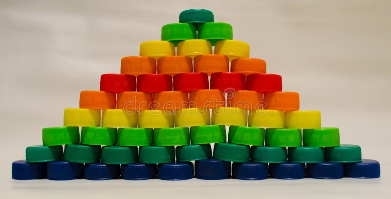 Colorful plastic bottle caps grouped on white background. Recycling and environmental care stock image