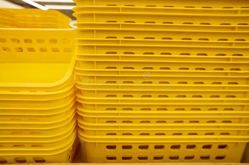 Colorful plastic boxes stacked one upon the other. Multi-colored plastic baskets on the store shelf stock photos