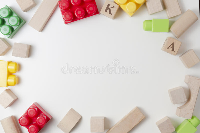 Colorful plastic construction blocks and wooden cubes on white background as kids toys frame. Flat lay. Top view stock photos