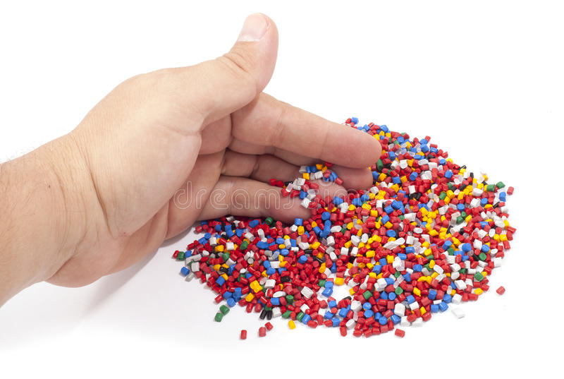 Colorful plastic polymer granules. And man hand on white stock photography