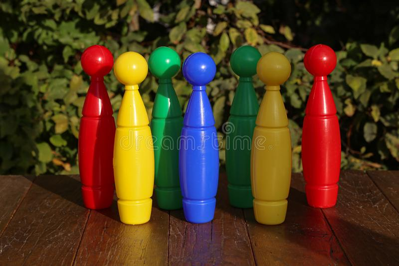 Colorful plastic toy bowling pins on wooden floor. Close up stock image