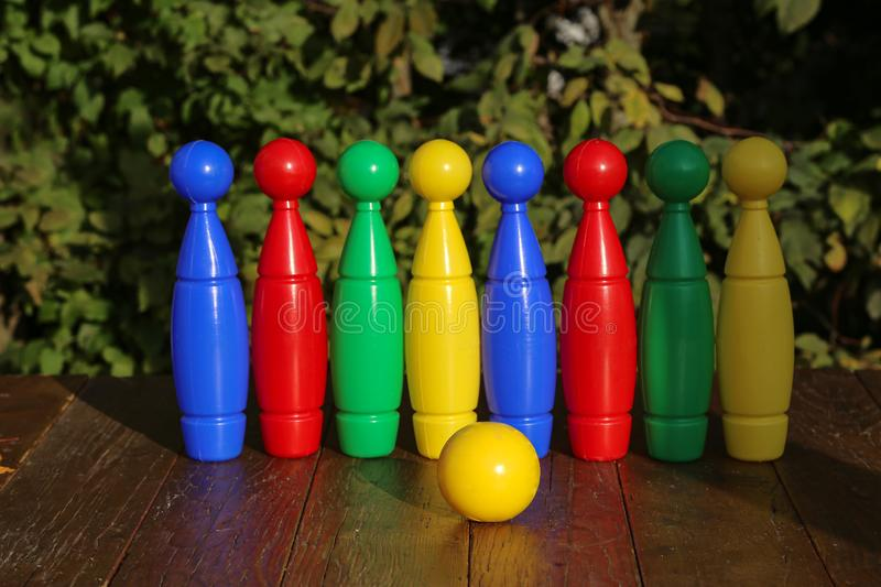 Colorful plastic toy bowling pins on wooden floor. Close up stock photo