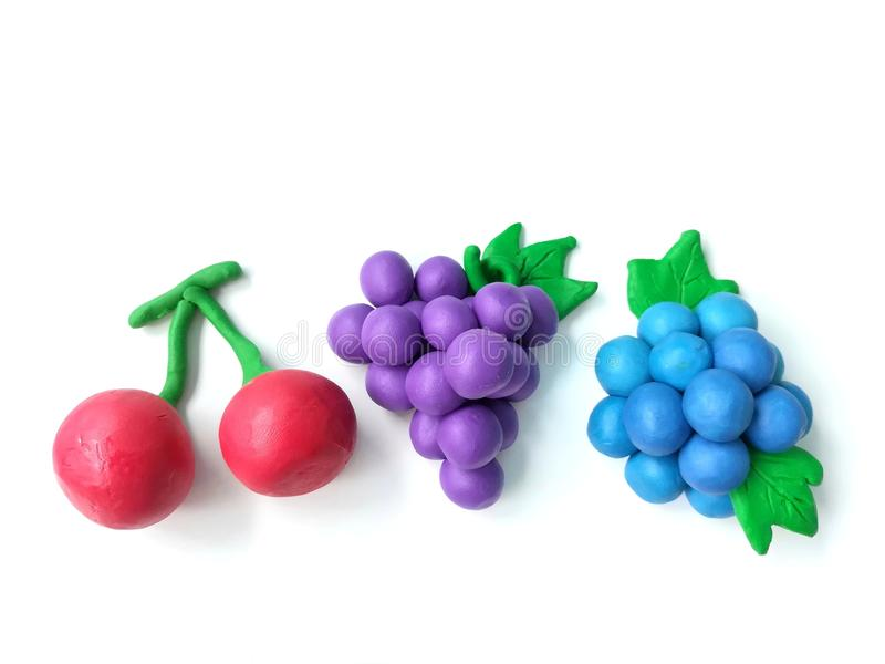 Colorful plasticine clay, handmade variety fruits, delicious cherry grapes blueberry dough royalty free stock photos