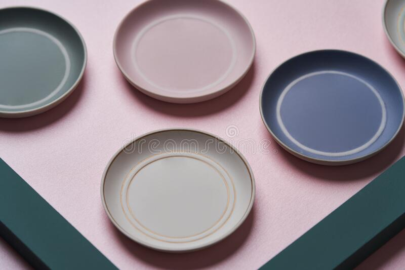 Colorful plates on pink background with copy space stock photo