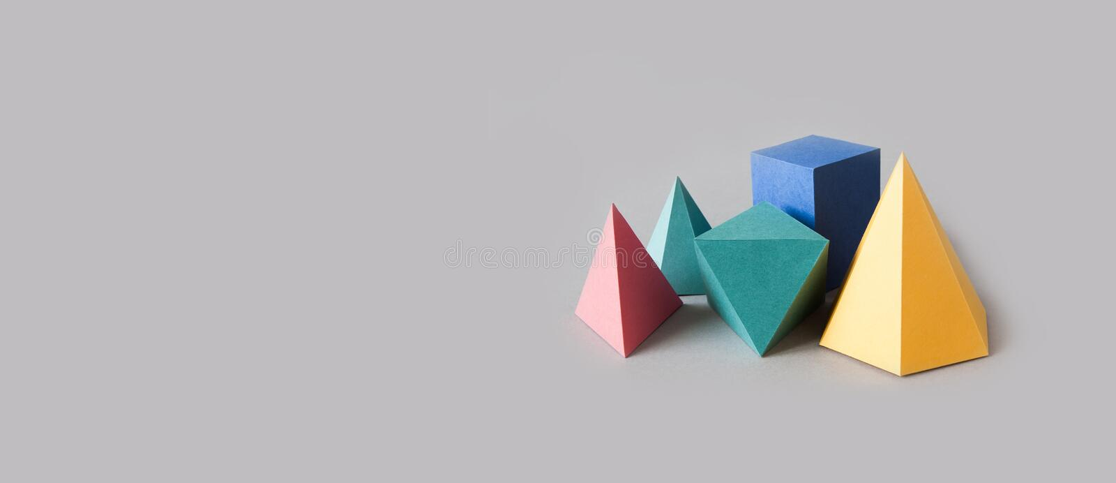 Colorful platonic solids, abstract geometric figures on gray background. Pyramid prism rectangular cube yellow blue pink. Green colored shapes. Shallow depth of royalty free stock photos