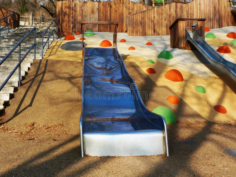 Colorful playground in hill side with rubber safety floor and slides stock images