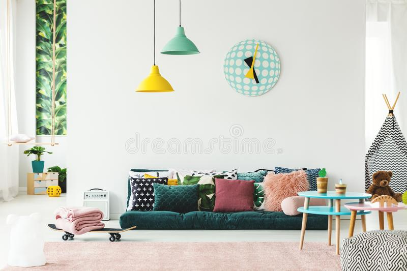 Colorful playroom with sofa. Colorful playroom interior with green sofa and pillows, skateboard and big clock on the wall royalty free stock photography