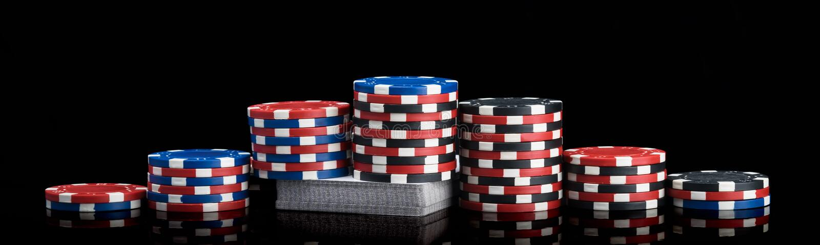 Colorful poker chips stand like a pyramid on a deck of cards on a black background. Colorful poker chips stand like  a pyramid on a deck of cards on a black stock image
