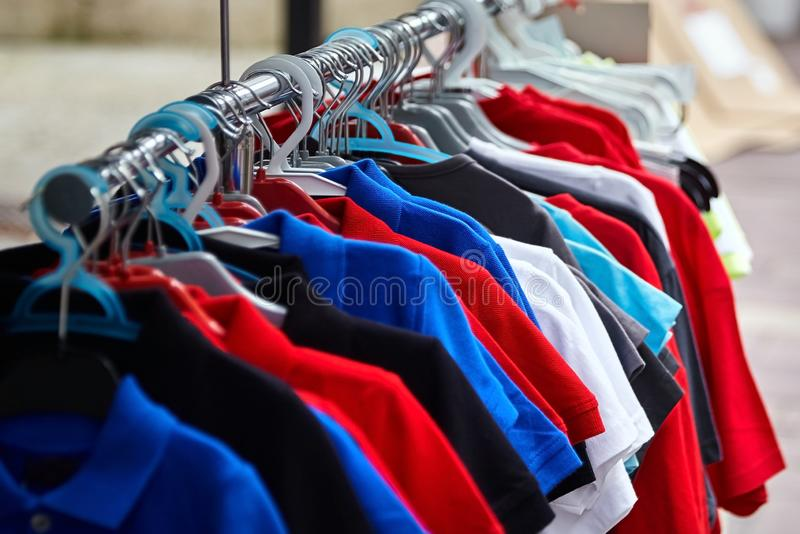 Colorful polo t-shirt for the man on hangers in shop stock photo