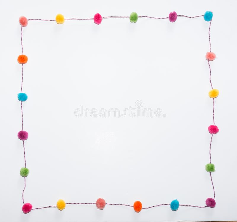 Pom Poms in a Square against a white background. Colorful pom poms in fuchsia, orange, yellow, coral, turquoise, green and purple arranged in a square against a royalty free stock photos