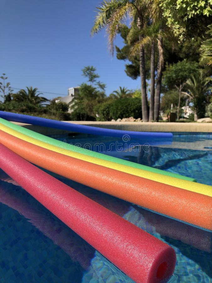 Colorful pool noodles on the poolside royalty free stock photos