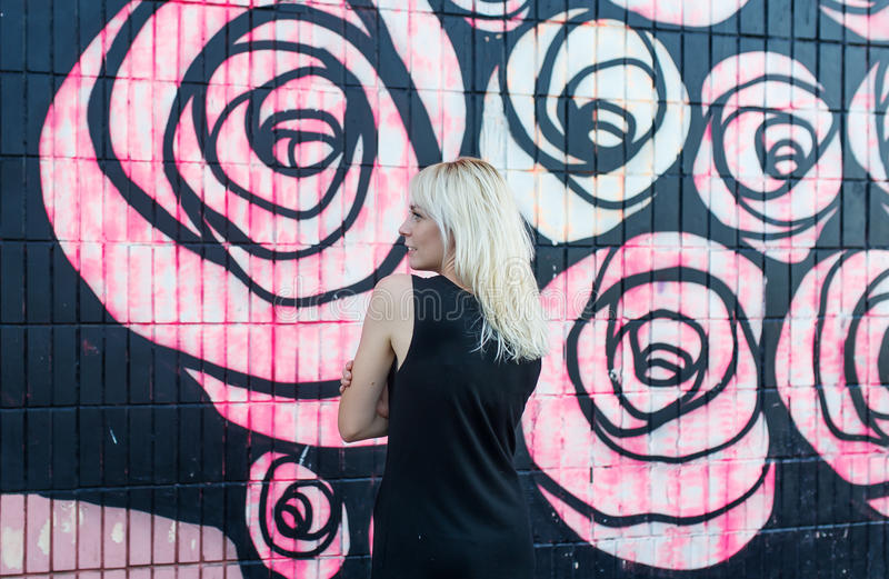 Colorful portrait of pretty young blond woman posing on graffiti wall background in black dress. In an abandoned house, Public place stock photography