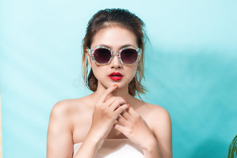 Colorful portrait of young attractive asian woman wearing sunglasses on blue. Summer beauty concept. royalty free stock photos