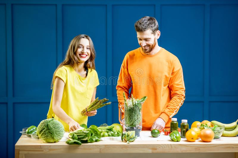 Colorful portrait of a yung couple with healthy food. Colorful portrait of a young couple in bright clothes making smoothie on the table full of green vegetables stock image