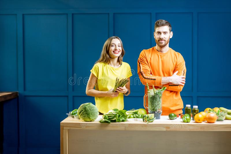 Colorful portrait of a yung couple with healthy food. Colorful portrait of a young couple in bright clothes making smoothie on the table full of green vegetables stock photography