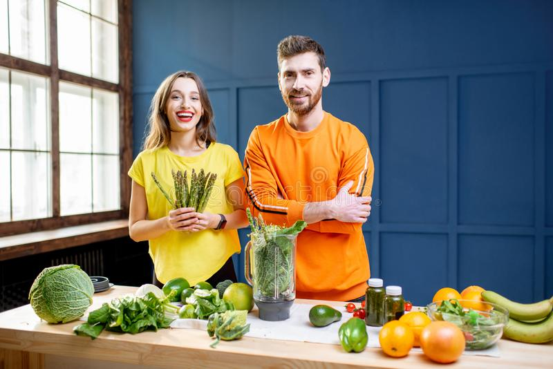 Colorful portrait of a yung couple with healthy food. Colorful portrait of a young couple in bright clothes making smoothie on the table full of green vegetables stock photo