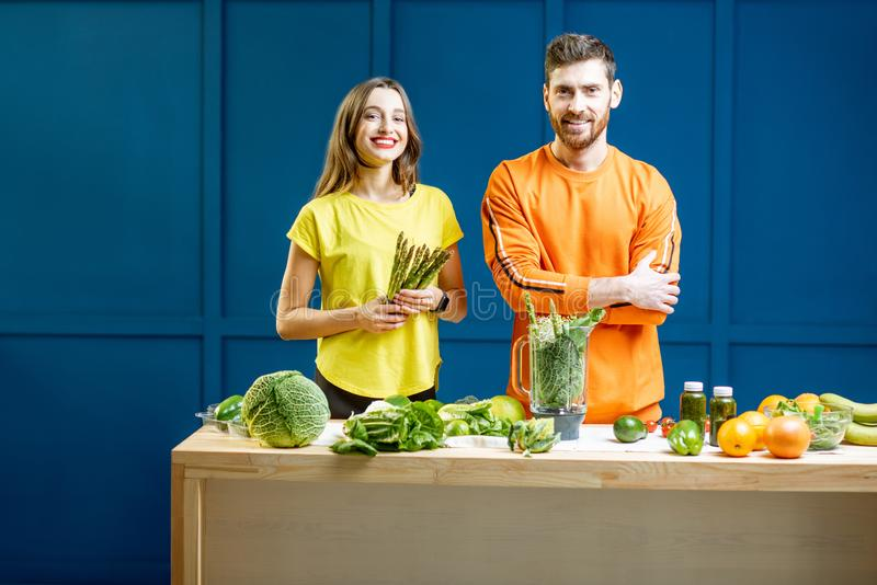 Colorful portrait of a yung couple with healthy food. Colorful portrait of a young couple in bright clothes making smoothie on the table full of green vegetables royalty free stock photography