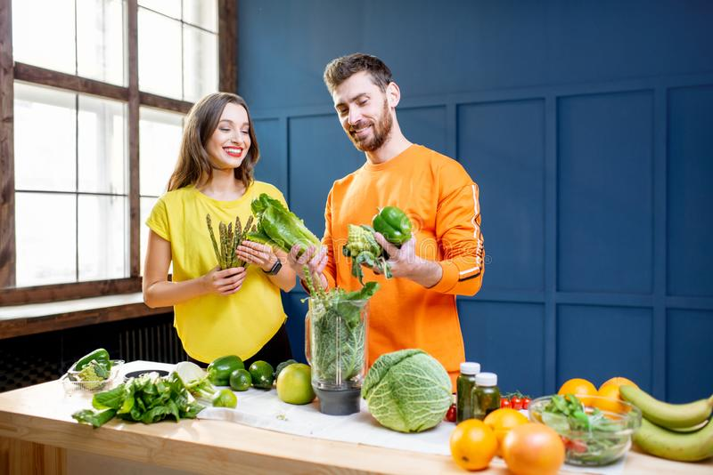 Colorful portrait of a yung couple with healthy food. Colorful portrait of a young couple in bright clothes making smoothie on the table full of green vegetables royalty free stock image