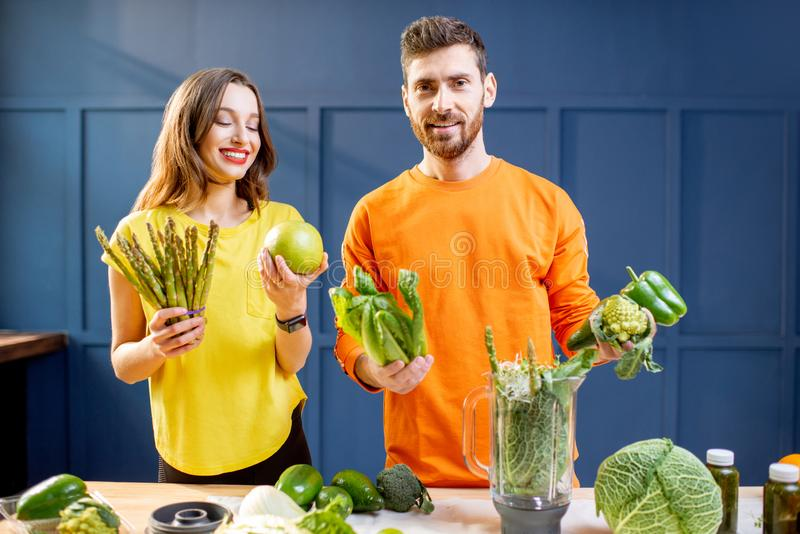 Colorful portrait of a yung couple with healthy food. Colorful portrait of a young couple in bright clothes making smoothie on the table full of green vegetables royalty free stock photo