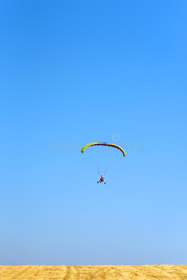 Colorful powered parachute against blue sky and yellow field. stock image