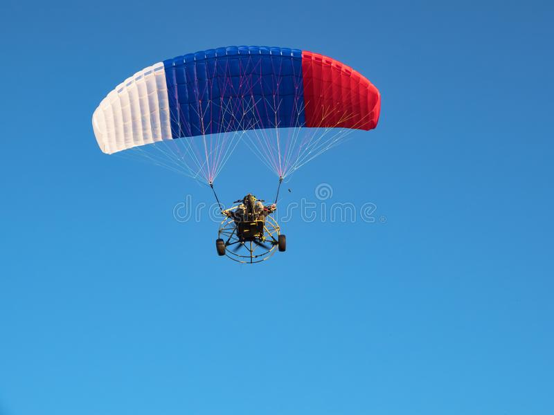 Colorful powered paraglider against blue sky. stock image