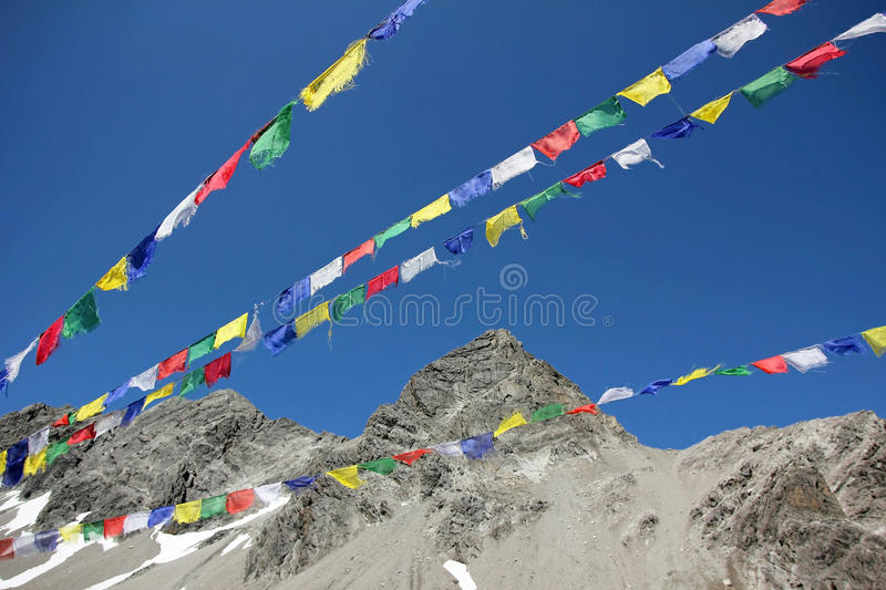 Colorful prayer flags and mountain peak against blue sky. Colorful prayer flags and glacier mountain peak against blue sky stock photo
