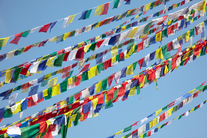 Colorful prayer flags over blue sky background. Colorful white, blue, yellow, green and red prayer flags over blue sky background. Buddhism prayers printed on stock photography
