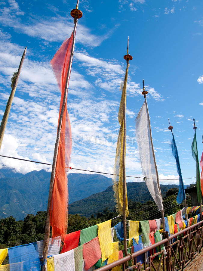 Colorful prayer flags over a clear blue sky near a temple in Bhutan royalty free stock photos