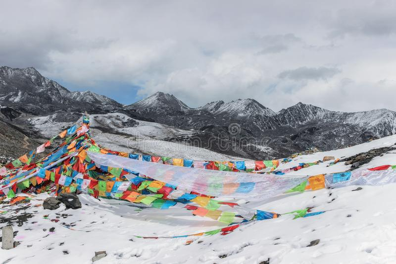 Colorful prayer flags on snow mountain stock photos