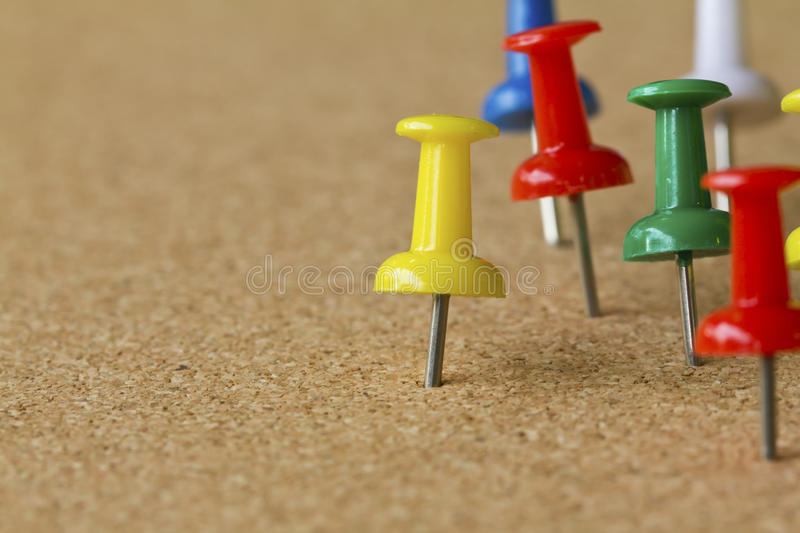 Colorful push pins on cork bulletin board. royalty free stock photos