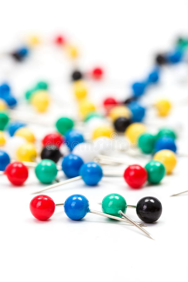Colorful push pins on white. Macro of colorful sewing push pins on white royalty free stock image