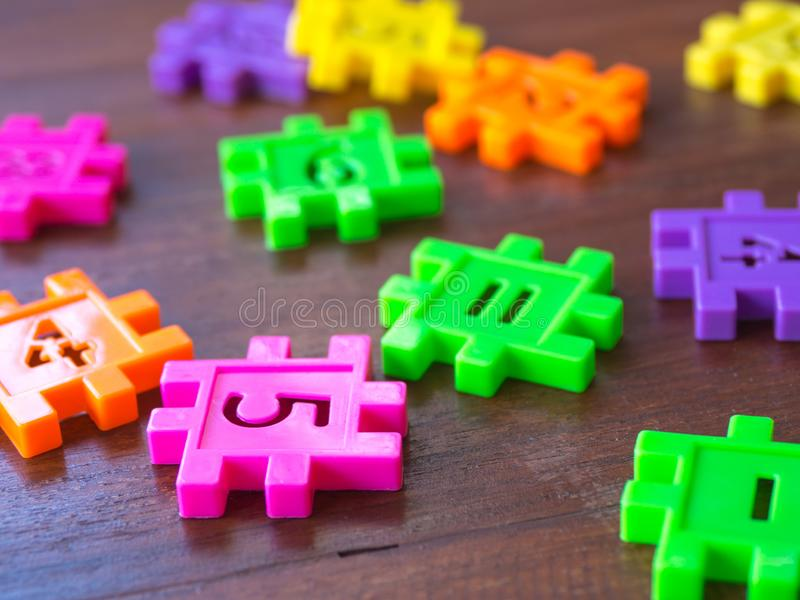 Colorful puzzle Jigsaw plastic number on the wooden table. Concept of education and math learning. stock images