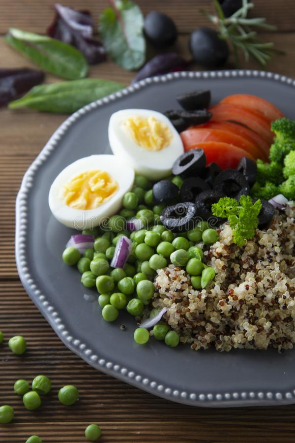 Colorful quinoa buddha plate withbroccoli, egg, spring onion, tomatoes and green peas. Home made food. Concept for a tasty and royalty free stock images