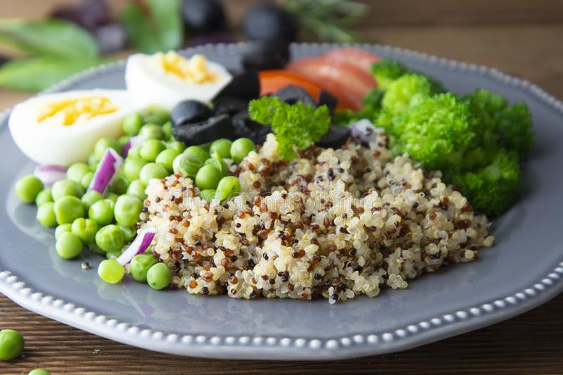 Colorful quinoa buddha plate withbroccoli, egg, spring onion, tomatoes and green peas. Home made food. Concept for a tasty and stock image
