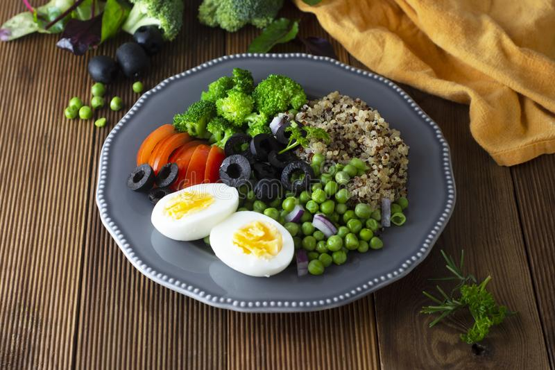 Colorful quinoa buddha plate withbroccoli, egg, spring onion, tomatoes and green peas. Home made food. Concept for a tasty and royalty free stock image