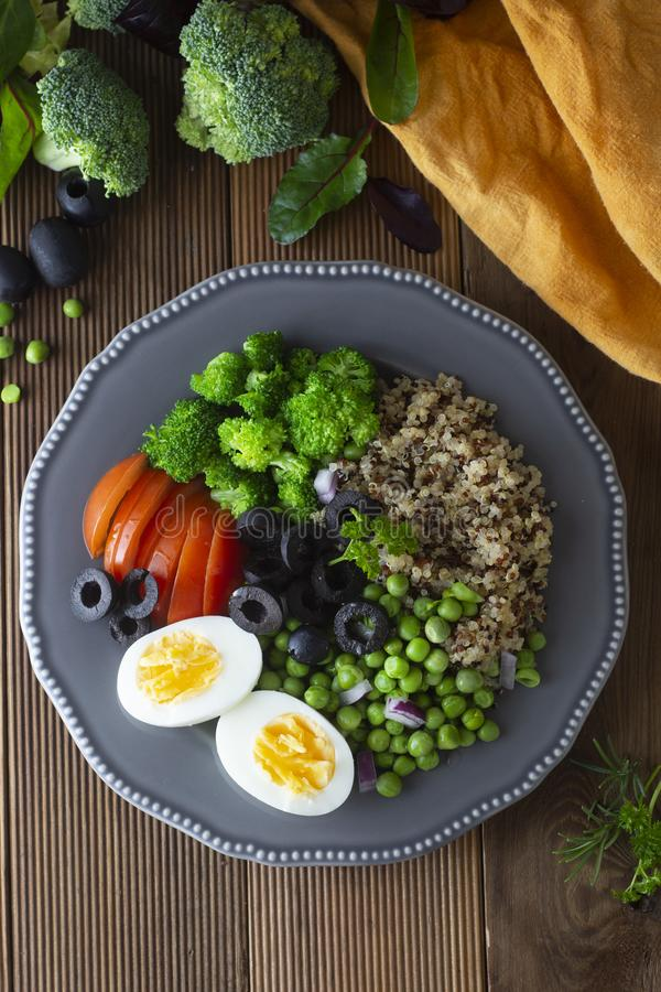 Colorful quinoa buddha plate withbroccoli, egg, spring onion, tomatoes and green peas. Home made food. Concept for a tasty and royalty free stock photo