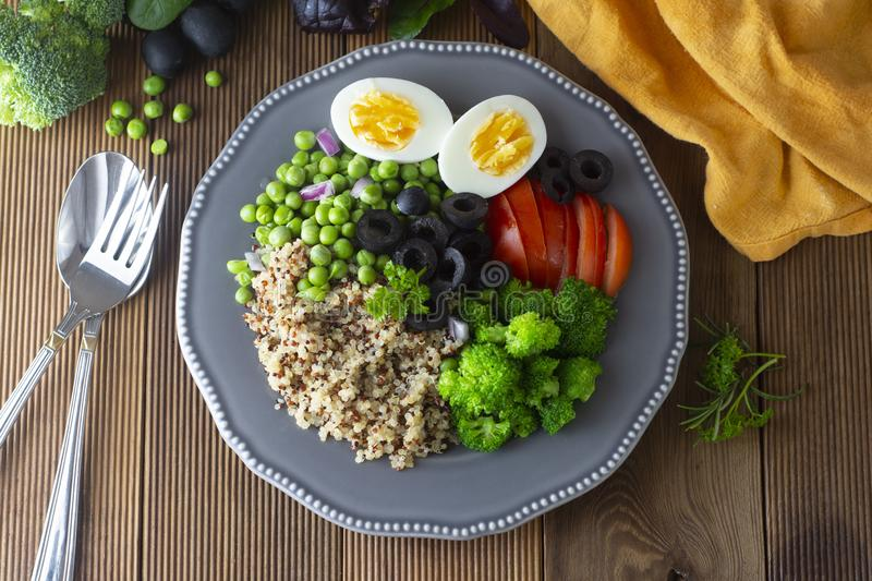 Colorful quinoa buddha plate withbroccoli, egg, spring onion, tomatoes and green peas. Home made food. Concept for a tasty and stock photos