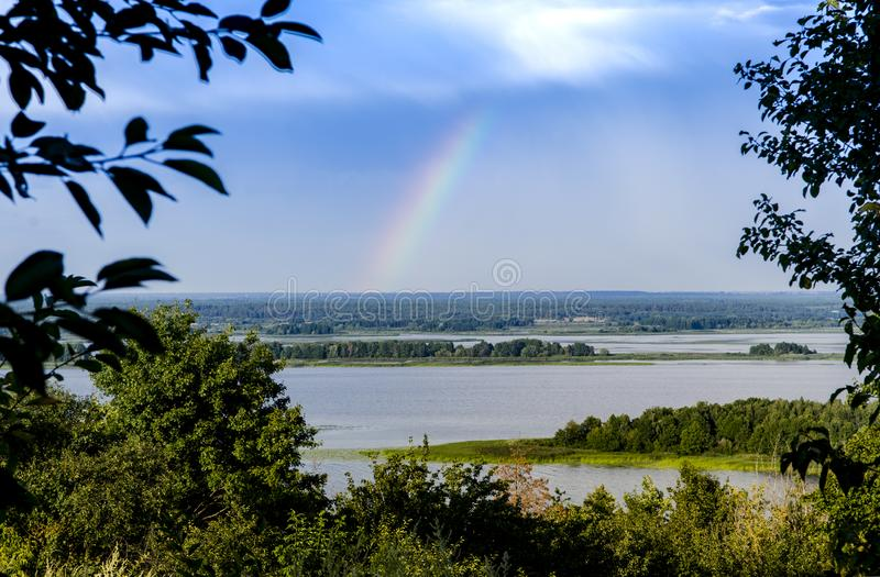 Colorful rainbow on the blue storm sky over a beautiful river. Colorful rainbow on the blue storm sky over a huge beautiful river, travel, spectrum, tourism stock photography