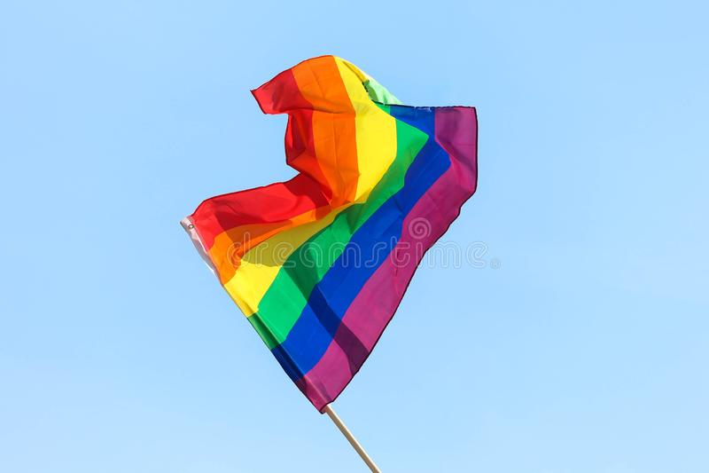 Colorful rainbow flag waving against a sunny blue sky background stock image