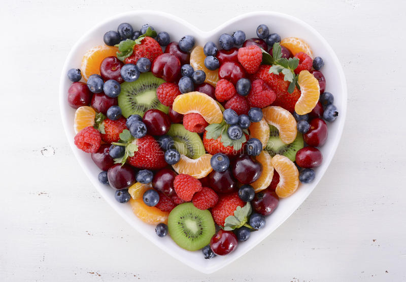 Colorful rainbow fruit in heart shape bowl. Colorful rainbow fruit including raspberries, strawberries, cherries, blueberries, mandarins and kiwi fruit in heart royalty free stock photography