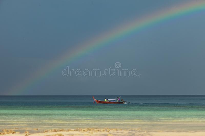 Colorful rainbow over a Tropical beach of Andaman Sea, Thailand. royalty free stock photo
