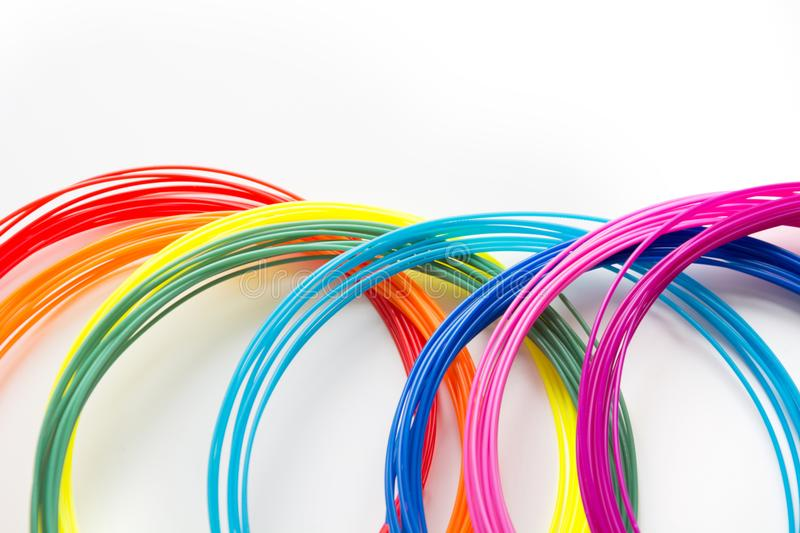 Colorful rainbow plastic filaments with for 3D pen laying on white. New toy for child. stock photos